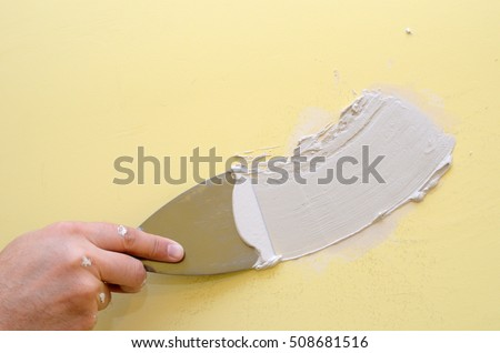 Hand with putty knife repair damaged wall #508681516