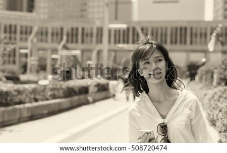 Happy japanese girl walking in Tokyo using her smartphone. #508720474