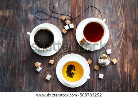 Tea, black tea, green tea, black espresso coffee in white porcelain cups on rustic wooden table. Top view. #508783252