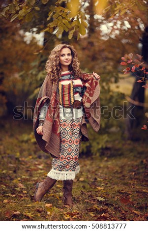 Portrait of cute blonde woman in the poncho outdoor. Boho fall style.