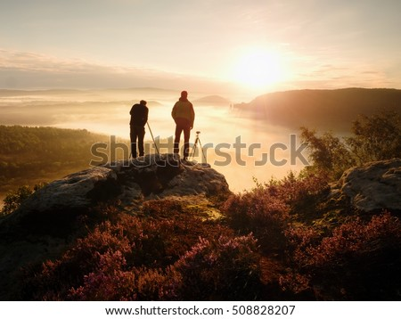Photographers stay on cliff and takes photos. Dreamy foggy mountains, orange misty sunrise in a beautiful valley below #508828207
