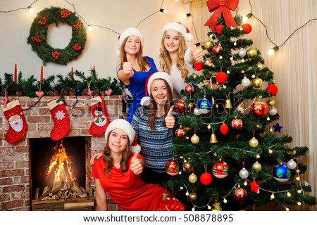 Friends near the Christmas tree holding a finger up next  in the room at Christmas. Beautiful girl celebrating New Year together. OK. #508878895