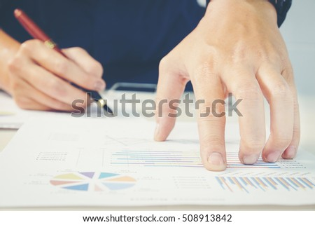 hand with a pen writing on the business paper. Report chart #508913842