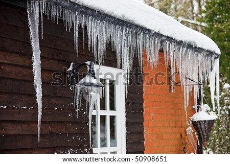 Icicles hanging from a lamp on the exterior of a panelled wooden house with a white windowed door. Photo has relatively short depth of field, with focus on the lamp covered with icicles. Royalty-Free Stock Photo #50908651