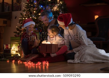 Christmas night. Near the christmas tree a lovely family opening their gifts. They enjoy the warm Christmas atmosphere in their living room, mom and kids wearing a hat of Santa Claus. #509093290