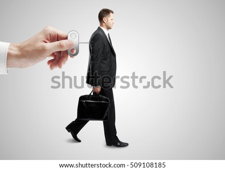Hand turning winder on business person's back. Grey background. Control concept #509108185