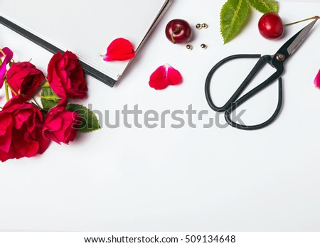 Red roses, cherries and scissors on the white background, top view #509134648
