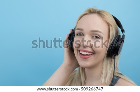 Young woman with headphones  listening to music and having fun against blue background #509266747
