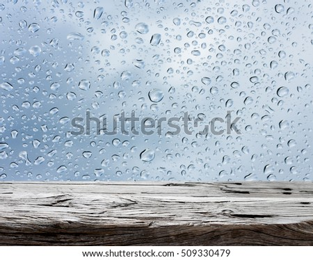 Old Wood table top on rain drops on clear window - can be used for display or montage your products #509330479
