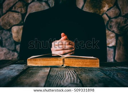 male in black clothes in front of an open old book. the concept of prayer, study, witchcraft. selective focus #509331898