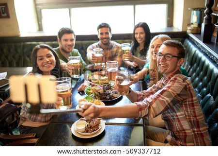 people, leisure, friendship and technology concept - happy friends taking picture by smartphone selfie stick, drinking beer and eating snacks at bar or pub #509337712