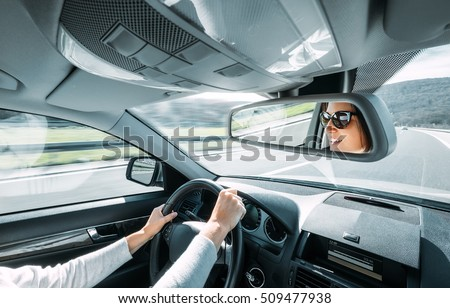 Woman drive a car reflects in back view mirror #509477938