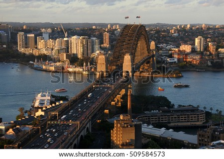 Aerial urban landscape view of Sydney Harbor bridge at sunset with North Sydney and The Rocks in Sydney New South Wales, Australia.  Royalty-Free Stock Photo #509584573