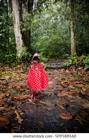 Asian Chinese little girl wearing raincoat in the tropical rain forest alone. #509588560
