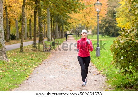 Attractive shapely young woman out jogging in a colorful autumn park approaching along a footpath in a healthy active lifestyle and fitness concept #509651578