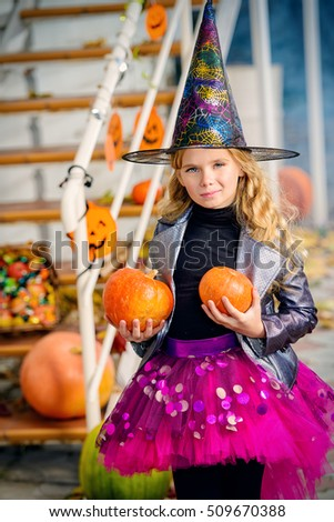 Beautiful little girl in a costume of witch celebrating halloween. Trick or treat. Halloween party. #509670388