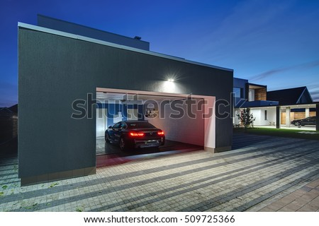 Entrance to a garage with the shining lamps in the modern country house. In the garage there is a black car with glowing parking lights. Around the house there is a tiled area. Horizontal. Royalty-Free Stock Photo #509725366
