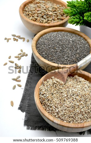 Wooden bowl filled with seeds of Sesame and fund other healthy seeds #509769388
