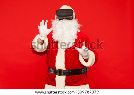 Santa Claus wearing virtual reality goggles, on a red background. Christmas #509787379