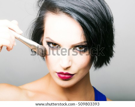 Sexy girl with short dark hair red lips and make up with face brush applies blush on her cheeks in front of grey background #509803393
