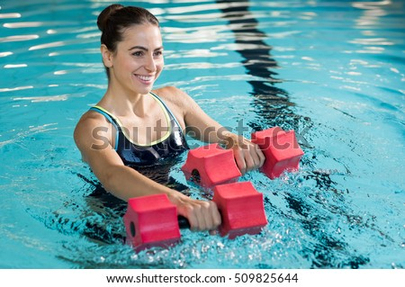Fit woman working out with foam dumbbell in swimming pool. Woman engaged in doing aqua aerobics in water. Young beautiful woman doing aqua gym exercise with water dumbbell in swimming pool. #509825644