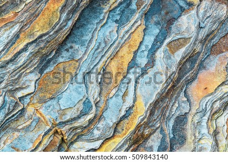 Rock layers - a colorful formations of rocks stacked over the hundreds of years. Interesting background with fascinating texture. Royalty-Free Stock Photo #509843140