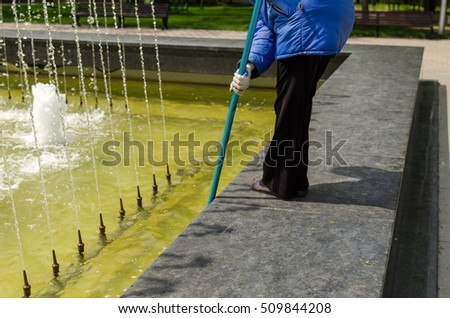 Woman in a blue coat is cleaning the fountain in the park #509844208