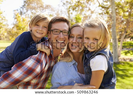 Parents carrying their two young kids in park look to camera #509863246