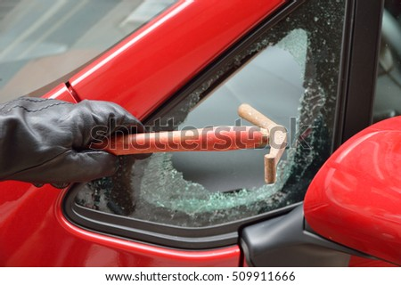 thief hitting the glass of a car to rob #509911666