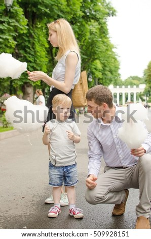 Young family is eating cotton candy in the park #509928151