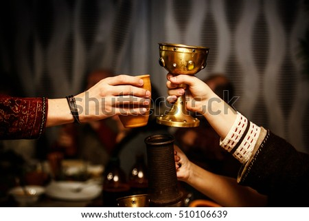 people clink by cups on a medieval feast. Royalty-Free Stock Photo #510106639