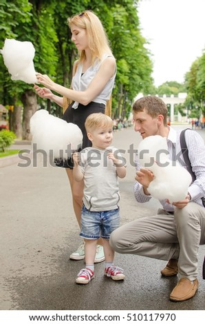Young family is eating cotton candy in the park #510117970