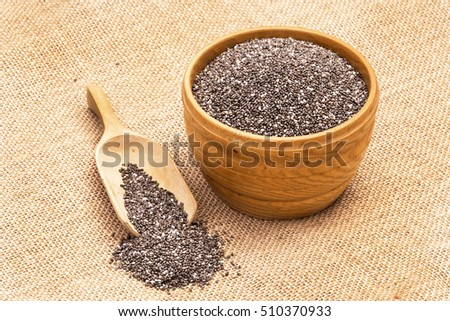 Wooden bowl full with chia seeds and a spoon next to it on sack cloth background seen from above #510370933