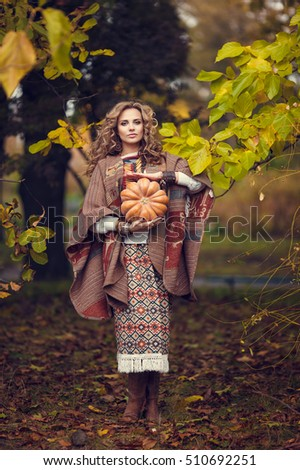 Cute blonde girl holding pumpkin in the poncho outdoor. Boho fall style.