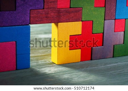 Move beyond. Glowing doorway, colorful wall of wooden puzzles. Move beyond meaning or definition.