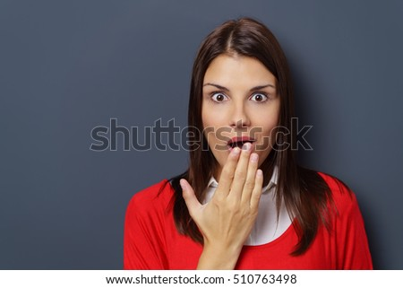 Shocked or amazed attractive young woman in a bright red top with her hand to her mouth and wide-eyed expression #510763498