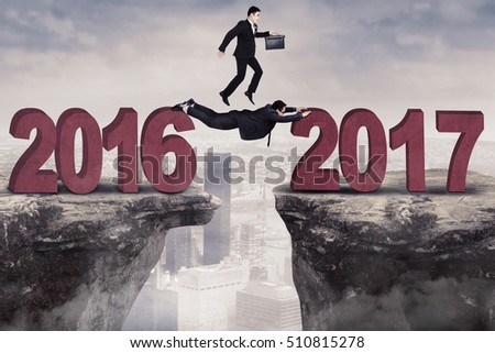 Male entrepreneur jumping on the gap towards number 2017 while carrying briefcase helped by his colleague #510815278