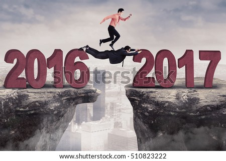 Image of two businessman work together to reach 2017 while jumping a gap on the cliff  #510823222