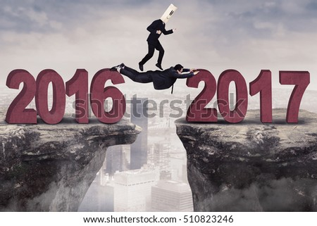 Image of two businessmen working together on the gap toward number 2017, shot outdoor #510823246