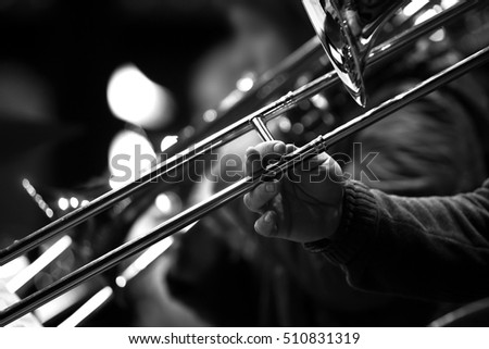 Hand of man playing the trombone in black and white #510831319