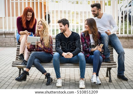Group of young people using smartphone and tablet computers outdoors in urban background. Women and men sitting on a bench in the street wearing casual clothes. #510851209