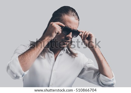 Stylish and handsome. Handsome young man in white shirt adjusting his sunglasses while standing against grey background #510866704