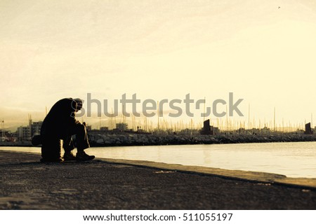 Sad old man sitting by the sea. Concept about people, sadness and loneliness