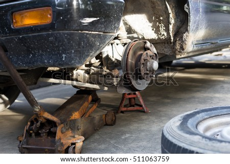Repair old car brake disk of the wheel hub with jack holds the body #511063759