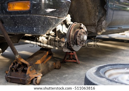 Repair old car brake disk of the wheel hub with jack holds the body #511063816