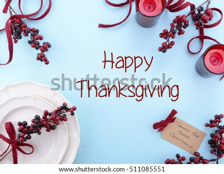 Thanksgiving pale blue wood background with decorated borders of red berries, and Happy Thanksgiving text.