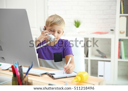 Little boy talking on phone at father's table in office #511218496