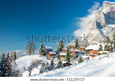 Travel to Switzerland in the winter. Alpine Village in the snow. Traditional houses with red shutters and roofs. #511239727