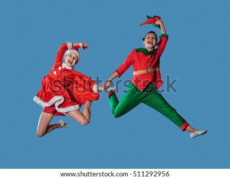 Jumping and flying funny kids in Peter pan and snow maiden costume isolated on blue background.