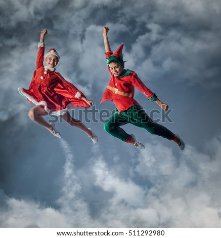 Funny kids in Peter pan and snow maiden costume flying in a sky.